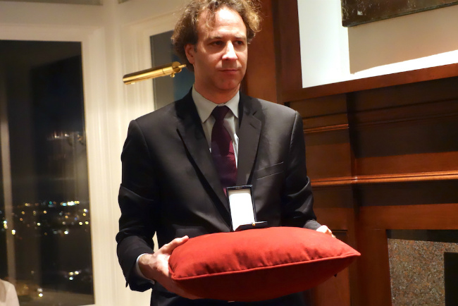 Gilles Delcourt (Deputy Cultural Attaché) holds the pillow with the medal.