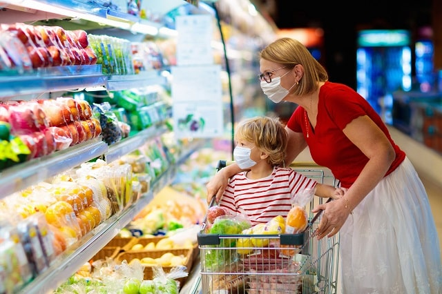 Shopping with kids during virus outbreak. Mother and child wearing surgical face mask buying fruit in supermarket.