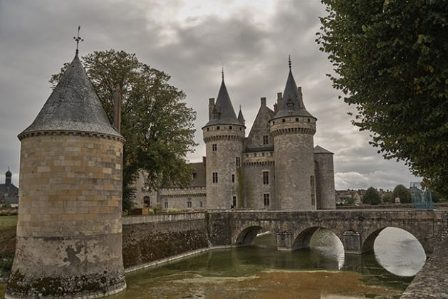 Conical-roofed towers and surrounding moat inspire tales of yore.